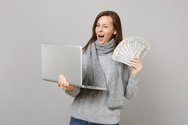 Knipperende vrouw in trui werkt op laptop pc-computer, houdt veel dollars bankbiljetten contant geld geïsoleerd op een grijze achtergrond. gezonde levensstijl online behandeling die het concept van het koude seizoen raadpleegt.