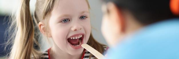 Kno-arts die een klein meisje met keelpijn in de kliniek onderzoekt