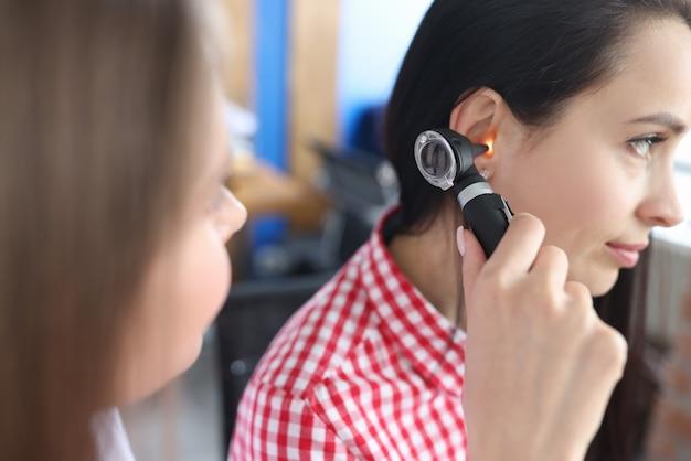 Kno-arts die gehoorproblemen van jonge vrouw diagnosticeert met behulp van otoscope