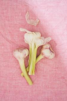 Knoflook arrangement op roze doek bovenaanzicht