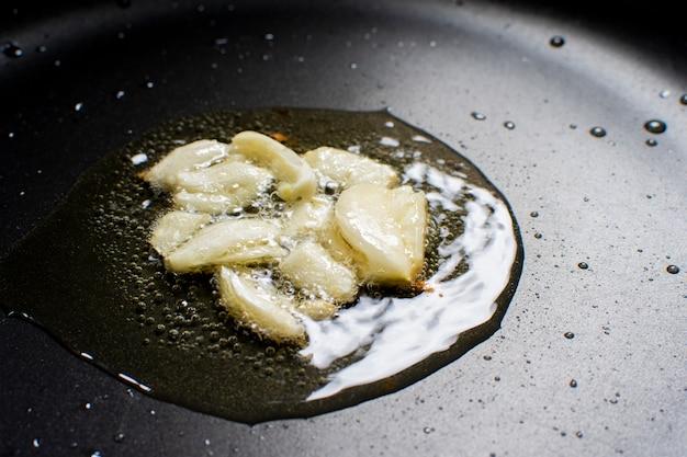 Knoflook braden op een plantaardige olie in een zwarte hete pan
