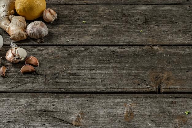 Knoflook, citroen, gember, folk remedies voor de verkoudheid in de linkerhoek op een houten tafel