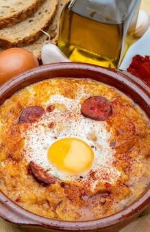 Knoflook- en broodsoep (castiliaans, uit spanje) in kleipot en de belangrijkste ingrediënten. uitzicht van boven.