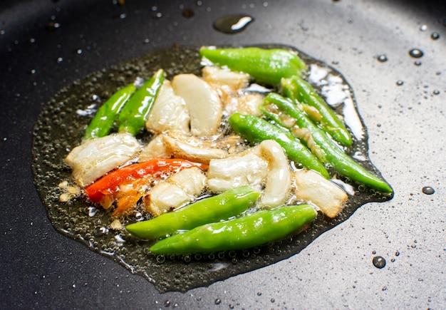 Knoflook en chili bakken op een plantaardige olie in een zwarte hete pan