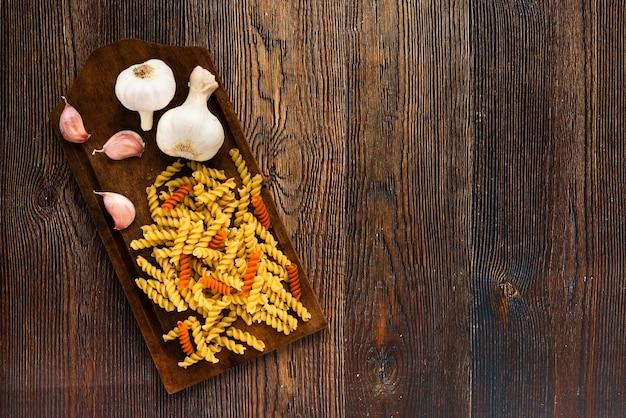 Knoflook en fusilli pasta op snijplank over houten gestructureerde achtergrond