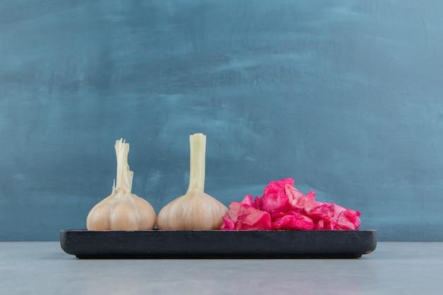 Knoflook en ingelegde rode kool op het bord