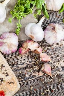 Knoflook en kruiden verse basilicum op de snijplank tijdens het koken, keukentafel tijdens het koken van voedsel, close-up