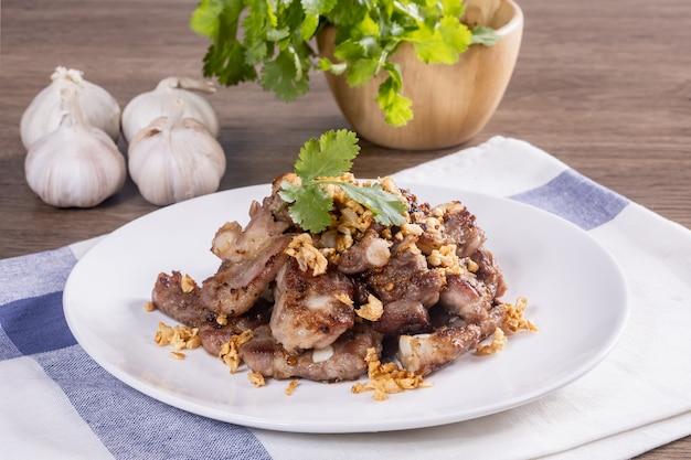 Knoflook en peper varkensvlees botten gebakken op een houten tafel