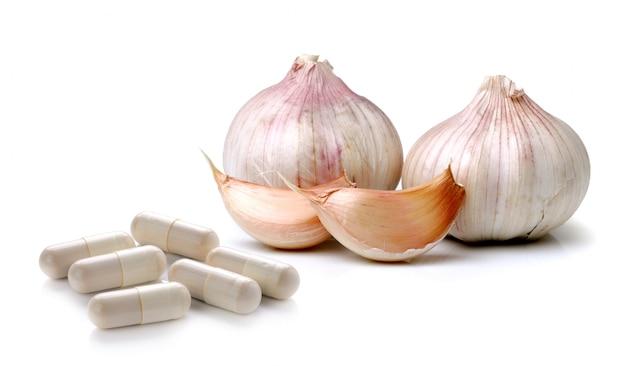 Knoflook en pillencapsule die op witte ruimte wordt geïsoleerd