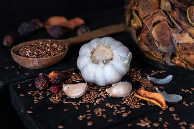 Knoflook, gedroogd fruit en zaden in een donkere, rustieke ondergrond. artistieke foto van knoflook en droog fruit op oude zwarte lijstschot in rustige ciaroscurro-stijl