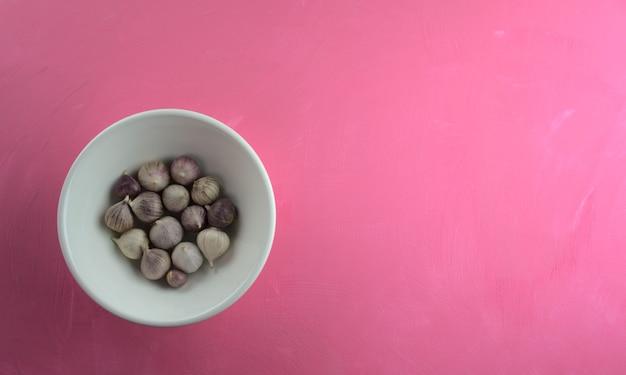 Knoflook in kom op acryl krassend roze canvas achtergrond