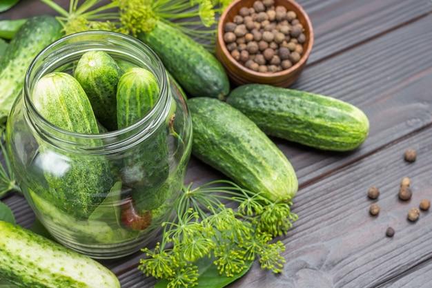 Knoflook, komkommers en kersen in glazen pot. komkommers en dille op tafel. zelfgemaakte fermentatieproducten. plat leggen