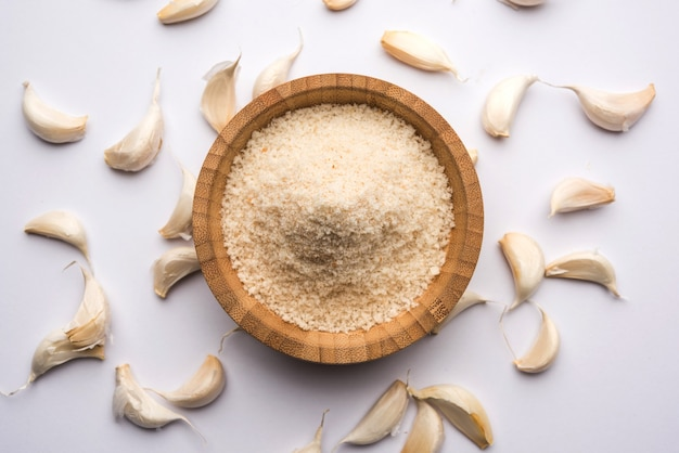 Knoflook of lahsun poeder is gemalen, gedroogde knoflook. het is een veelgebruikte smaakmaker voor pasta, pizza en gegrilde kip. over witte achtergrond, selectieve focus
