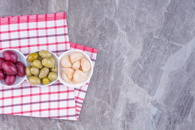Knoflook, pruimen en olijfolie op een schaal op een theedoek, op het marmer.