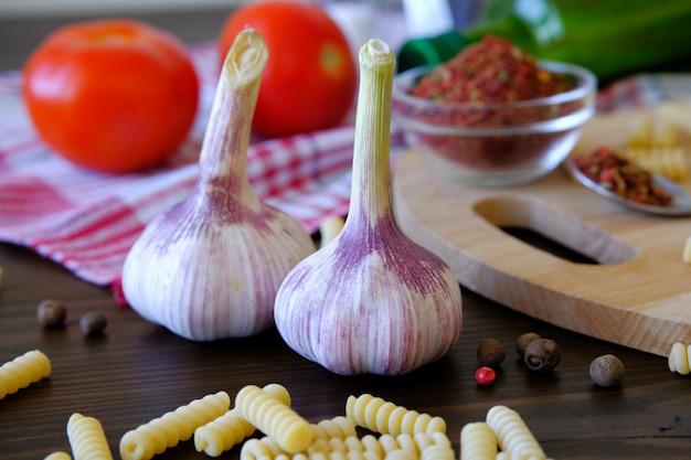 Knoflook, rode tomaten, droge georgische kruiden voor fijnproevers, olijfolie, pasta op een houten tafel.