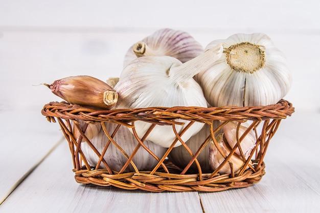 Knoflookteentjes en knoflookbol in een mand op een witte houten lijst.