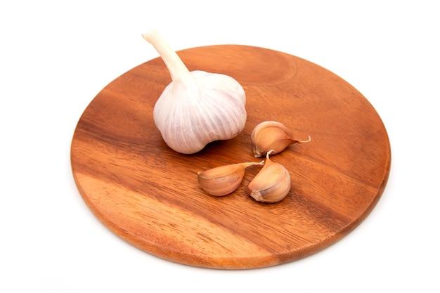 Knoflookteentjes en knoflookbol op een houten snijplank