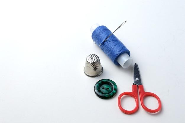 Knoop, een klosje draad met een naald, een vingerhoed, een kleine schaar en een knoop