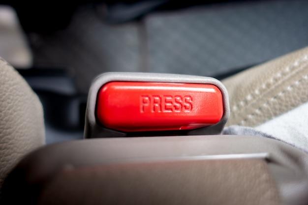 Knopen van de autogordelsluiting in de auto indrukken en loslaten