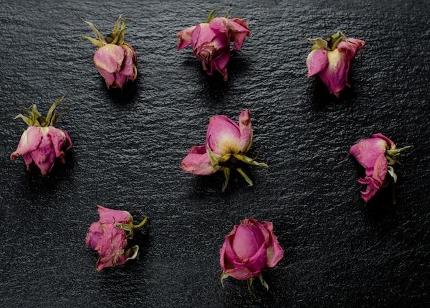 Knoppen van roze vervaagde droge rozen verspreid over een zwarte leisteen achtergrond