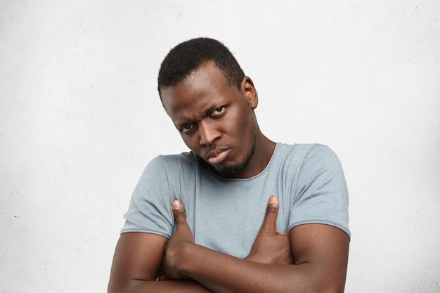 Knorrige en ontevreden jonge afro-amerikaanse man met casual grijs t-shirt fronst, armen gekruist, pruilend en kijkend met boze gekke uitdrukking, ontevreden over iets