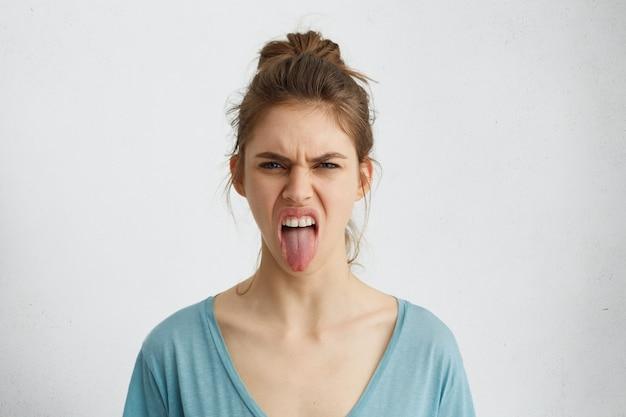 Knorrige vrouw met haarknoop die haar tong toont die negatieve emoties uitdrukt. woedende vrouw die haar walging toont terwijl ze ruzie heeft