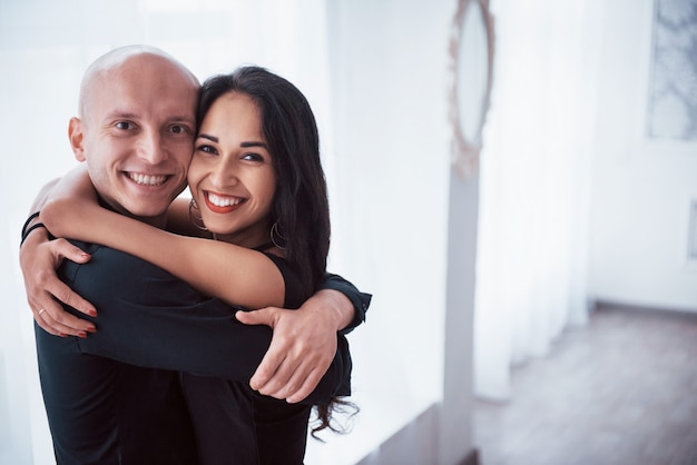 Knuffel elkaar en lachend. portret van gelukkige paar binnenshuis. kale man en brunette vrouw staat in de witte kamer