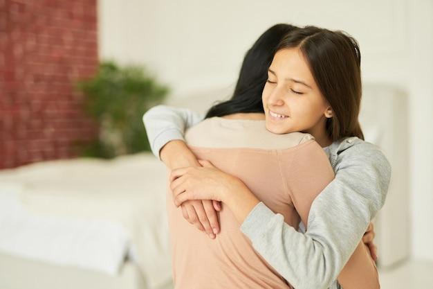 Knuffel je moeder schattig tienermeisje knuffelt haar moeder en kijkt aanhankelijk terwijl ze samen poseert op