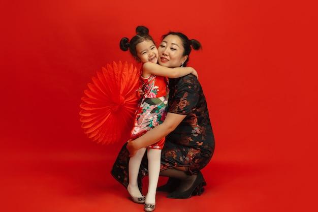 Knuffelen, blij lachend. gelukkig chinees nieuwjaar 2020. aziatisch moeder en dochterportret dat op rode achtergrond in traditionele kleding wordt geïsoleerd. viering, menselijke emoties, vakantie. copyspace.