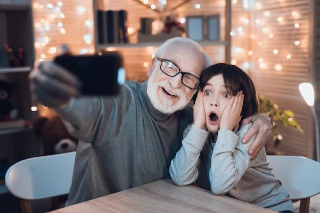 Knuffelen grootvader en kleinzoon maken selfie
