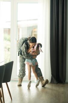 Knuffelen heroïsche moeder. dochter in jurk die haar heldhaftige moeder omhelst terwijl ze naar huis terugkeert