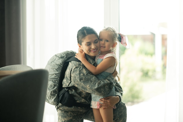 Knuffelen mooi meisje. rijpe militaire vrouw die een rugzak draagt en haar lieftallige mooie meid knuffelt
