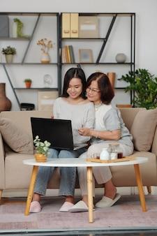 Knuffelen van gelukkige aziatische moeder en dochter zittend op de bank met laptop en aankopen doen in de online winkel