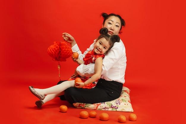Knuffelen, vrolijk glimlachen, lantaarns vasthouden. gelukkig chinees nieuwjaar 2020. aziatisch moeder en dochterportret op rode achtergrond in traditionele kleding.
