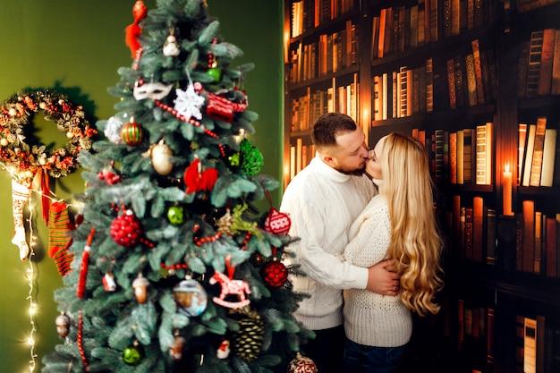 Knuffelend paar staat voor een kerstboom