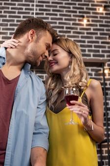 Knuffelend vriendje. krullend stralende aantrekkelijke vrouw knuffelt haar knappe vriendje terwijl ze rode wijn drinkt
