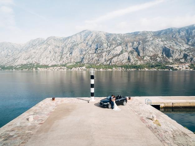 Knuffelende pasgetrouwden staan naast een zwarte cabriolet op de pier tegen de zee