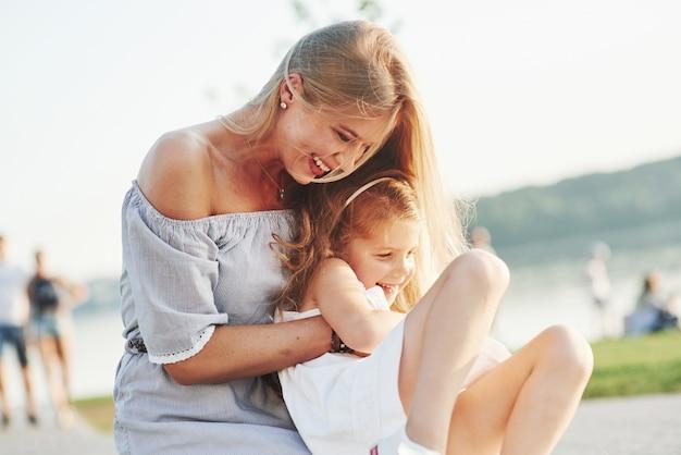 Knuffels en kriebels. foto van jonge moeder en haar dochter die goede tijd hebben op het groene gras met meer bij achtergrond.