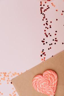 Knutselenvelop naast karamelharten en een rieten mand in pastelroze kleuren. valentijnsdag achtergrond.
