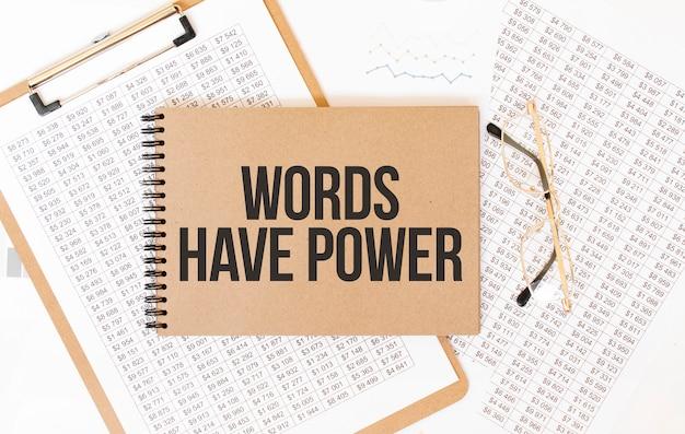 Knutselkleurenblok met tekst words have power notepad met brillen en tekstdocumenten. bedrijfsconcept