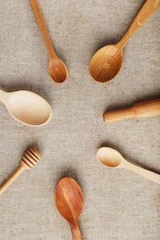 Knutsellepels van verschillende houtsoorten liggen op een rij op een hennep jute stof