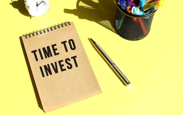 Knutselpapier notitieboek met tekst time to invest met briefpapier. gele achtergrondkleur.