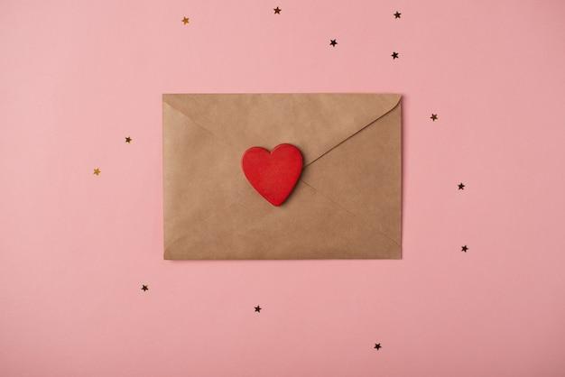 Knutselvelop met een rood hart op de roze achtergrond met sterretjes. romantische liefdesbrief voor valentijnsdag concept. bovenaanzicht.