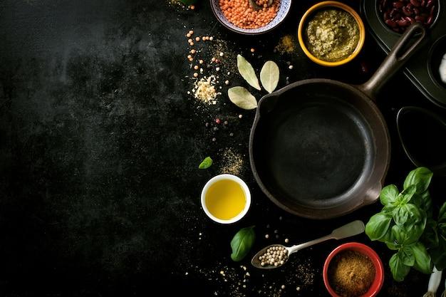 Koekenpan lege met diverse kruiden in een zwarte tafel