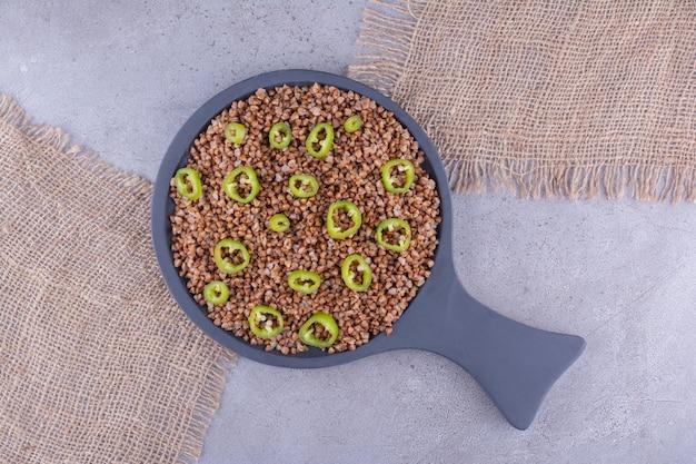 Koekenpan met boekweit en peperschijfje topping op stukjes stof op marmeren achtergrond. hoge kwaliteit foto