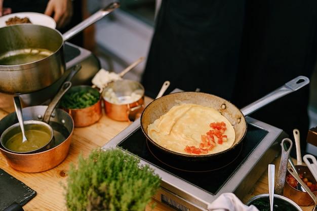 Koekenpan met een pannenkoek op het fornuis tijdens het koken in de keuken met metalen pollepels met voedsel