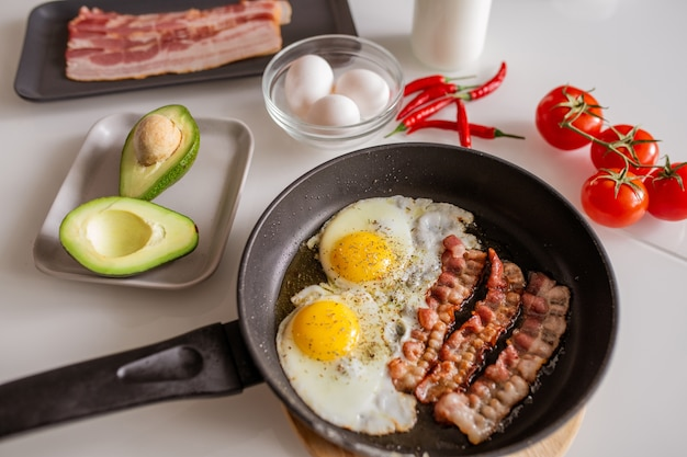Koekenpan met gebakken eieren en spek bestrooid met kruiden, verse avocado, rode rijpe tomaten en hete chili peper op de keukentafel geserveerd