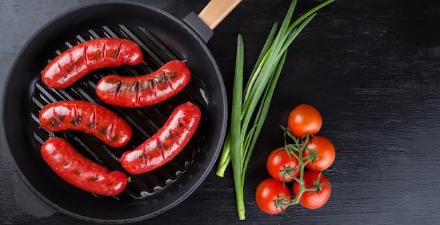Koekenpan met gebakken worstjes en tomaten met uien