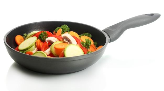 Koekenpan met groenten op wit