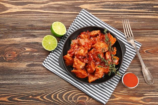 Koekenpan met heerlijke kip tikka masala op houten tafel